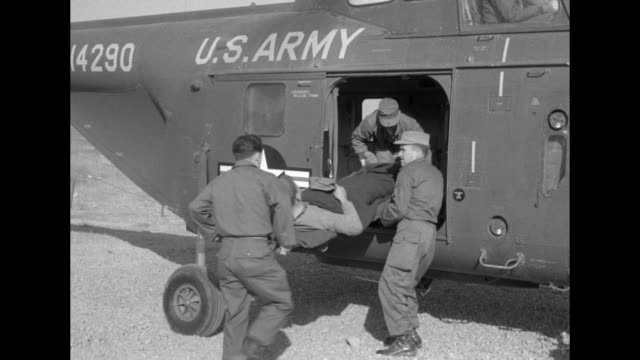 soldiers carry wounded north korean and red chinese soldiers on stretchers, load them onto us army helicopter / note: exact day not known - war stock-videos und b-roll-filmmaterial