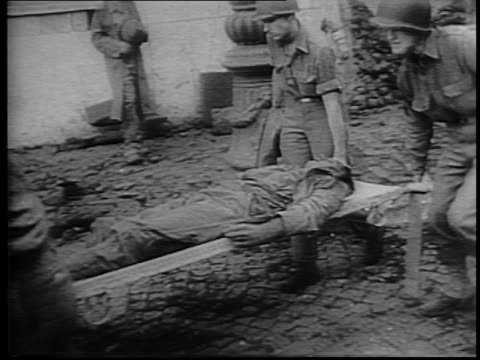 soldiers carry wounded on stretchers through street in naples / wounded civilian sits on curb bleeding from the head / montage of dead bodies in the... - bombardamento video stock e b–roll
