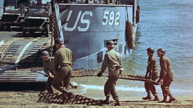 pan soldiers carrying and placing traction mats beneath lowered ramp of lct beached in low water - landungsboot stock-videos und b-roll-filmmaterial