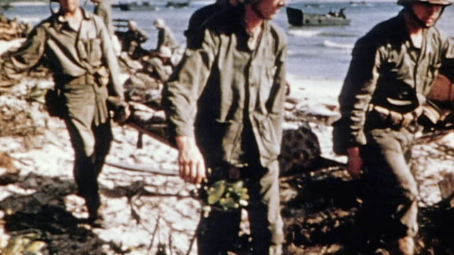soldiers carrying casualty on stretcher and assisting wounded soldiers walking on beach / iwo jima japan - schlacht um iwojima stock-videos und b-roll-filmmaterial