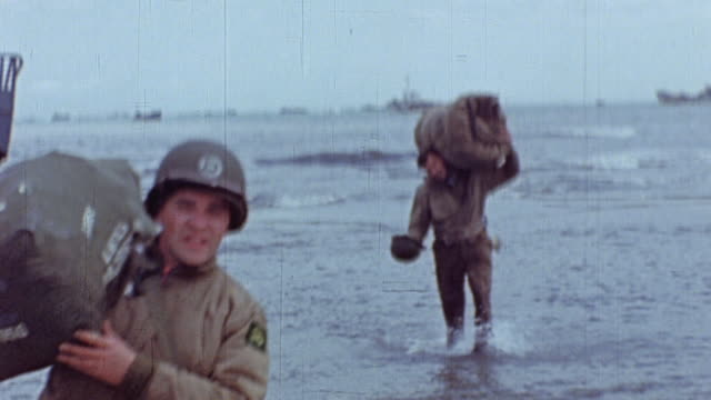 soldiers carrying duffel bags through the shallows from landing craft to beach and digging defensive trenches, and landing craft beached and anchored... - 1944 stock videos & royalty-free footage