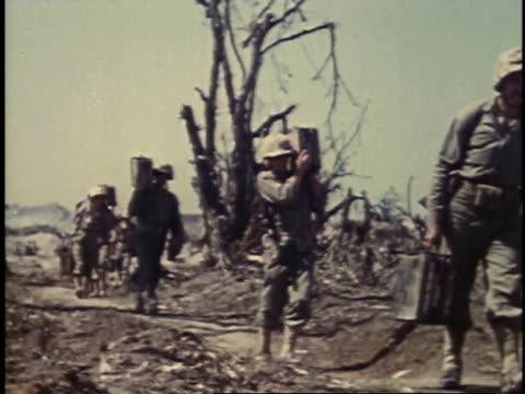 soldiers carrying supplies and man on a stretcher / iwo jima, japan - battaglia di iwo jima video stock e b–roll