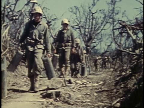 soldiers carrying supplies / iwo jima, japan - battaglia di iwo jima video stock e b–roll