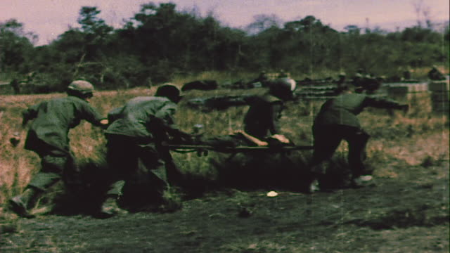 soldiers carrying wounded and escorting prisoners of war to chinook helicopters / vietnam - guerra del vietnam video stock e b–roll