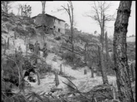 Soldiers carrying wounded man on stretcher down a hill / Italy