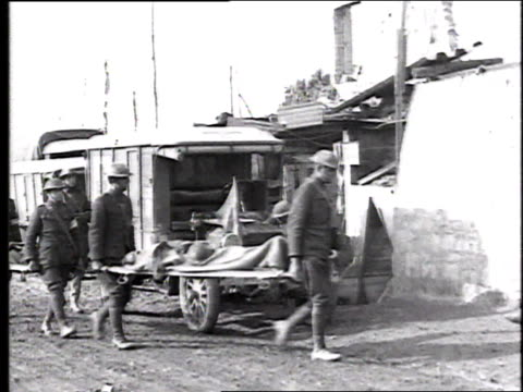 soldiers carrying wounded on stretchers from an ambulance into a red cross relief station / france - red cross stock videos & royalty-free footage