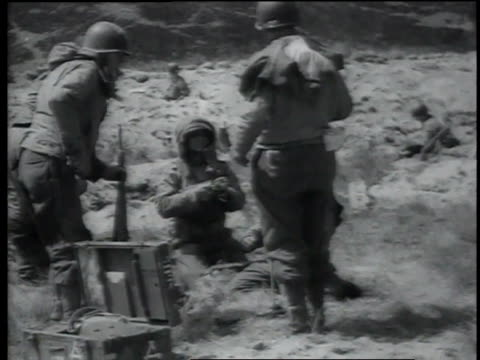 soldiers check their weapons and ammunition, one reads a pamphlet, and a tank drives across the land / normandy, france - d day stock videos & royalty-free footage