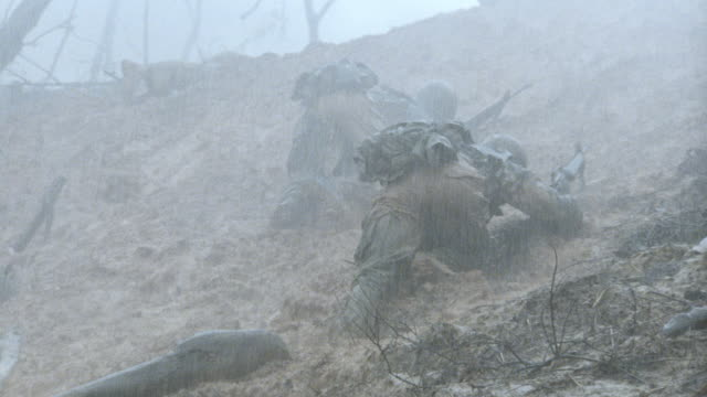 soldiers crawl up a muddy embankment in the rain during the vietnam war. - vietnam war stock videos & royalty-free footage