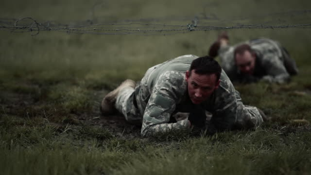 vídeos de stock, filmes e b-roll de soldiers crawling under low barbed wire at an obstacle course at a training, it's muddy. - campo de treinamento militar
