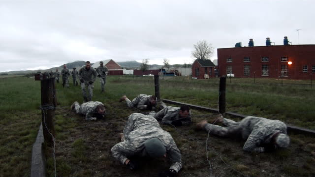 vídeos de stock e filmes b-roll de soldiers crawling under low barbed wire at an obstacle course at a training. - treino militar
