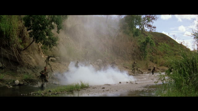 ws soldiers crossing jungle stream under heavy fire - gun stock videos & royalty-free footage