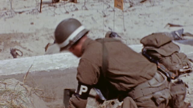 soldiers digging foxholes, drinking from canteens, and preparing encampment on green beach / normandy, france - 1944 stock-videos und b-roll-filmmaterial