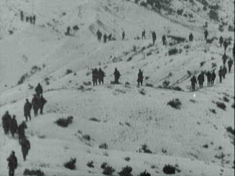 montage soldiers digging trench in deep snow and marching through mountainous countryside during korean war / korea - 掘る点の映像素材/bロール