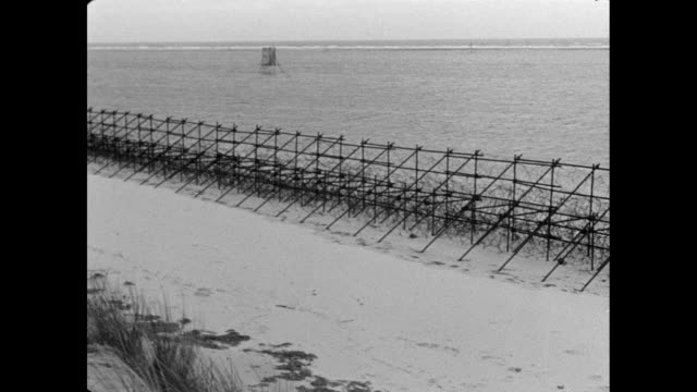 montage soldiers disassembling scaffolding and barbed wire fencing along a beach / england, united kingdom - dismantling stock videos & royalty-free footage