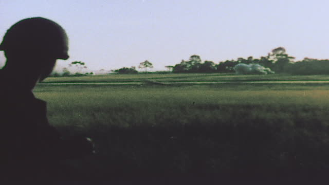 soldiers disembarking from uh1 hueys and chinook helicopters and infantry advancing across field / vietnam - 降り立つ点の映像素材/bロール