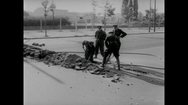soldiers drill into the ground across from the brandenburg gate in berlin - 1961 stock-videos und b-roll-filmmaterial
