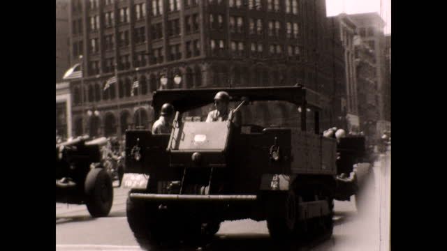 soldiers driving military trucks down the street with crowds of people and high rises on both sides; tracking views of tanks and cannons manned by... - heavy goods vehicle stock videos & royalty-free footage
