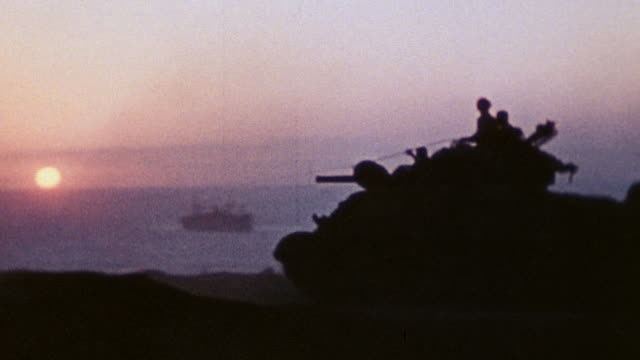 soldiers driving tanks jeeps and other military vehicles near coast as sun rises over horizon / iwo jima japan - battle of iwo jima stock videos and b-roll footage