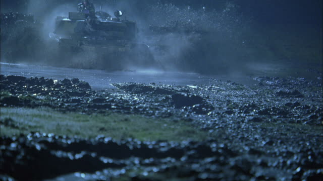 vídeos de stock, filmes e b-roll de ts, ms, cu, slo mo, soldiers driving tanks through mud in rain at night, usa - forma da água