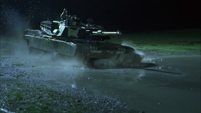 ms, pan, slo mo, soldiers driving tanks through mud puddle in rain at night, usa - armored tank stock videos & royalty-free footage