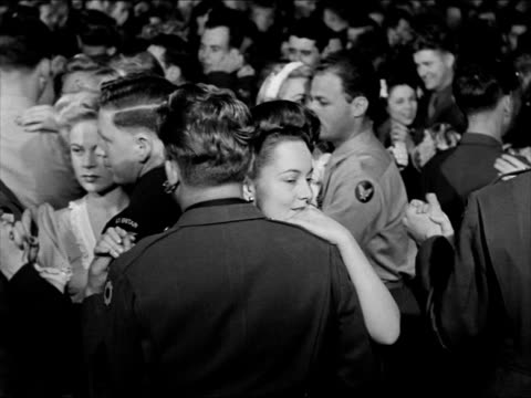 vídeos de stock, filmes e b-roll de soldiers entering building ws crowded dance floor soldier dancing w/ olivia dehavilland sailor dancing w/ marlene dietrich soldier dancing w/ deanna... - 1943