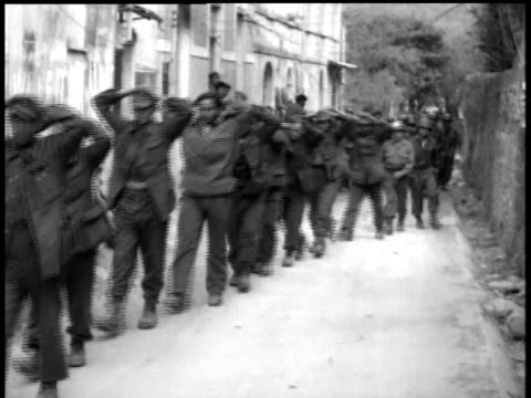 Soldiers escorting prisoners of war down a street / Italy