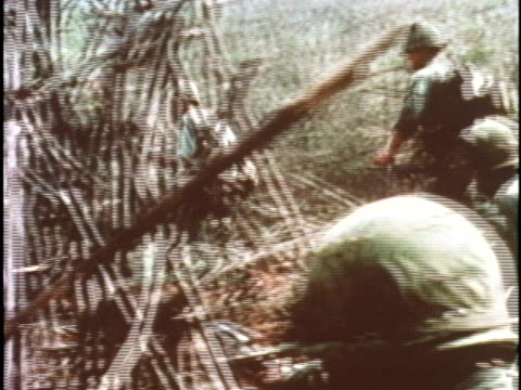 soldiers exit a helicopter on the ground and run through the jungle in vietnam - vietnamkrieg stock-videos und b-roll-filmmaterial