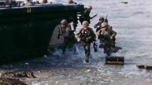 s soldiers exiting lvt landing craft wading through shallow water and advancing on the beach carrying weapons and supplies during wwii battle of... - landing craft stock videos & royalty-free footage