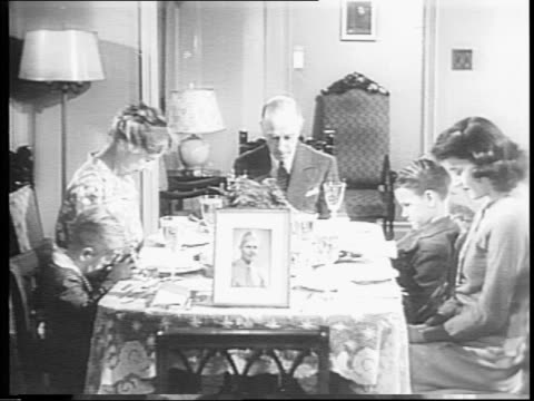 A soldier's family celebrating Thanksgiving Day without him / a woman picks up a framed photo and places it on the Thanksgiving dinner table /...