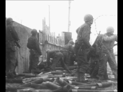 stockvideo's en b-roll-footage met soldiers fire artillery during world war ii battle for cherbourg / barbed wire in foreground and explosion in background / explosion and smoke near... - prikkeldraad