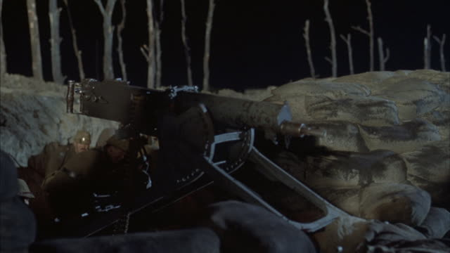 Soldiers fire weapons while taking cover in a trench.