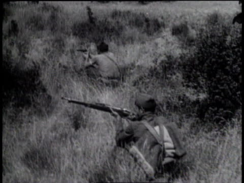 stockvideo's en b-roll-footage met soldiers firing cannons / soldiers firing guns / plane dropping a bomb / bomb exploding / soldiers running, firing, and falling dead - 1936