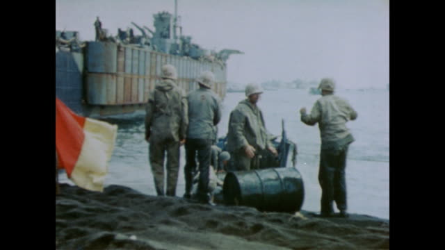 soldiers flag carrier vessel into shore / soldiers roll supplies from ship onto beach / soldiers use cranes and tanks to bring supplies, probably oil... - 1944 stock-videos und b-roll-filmmaterial