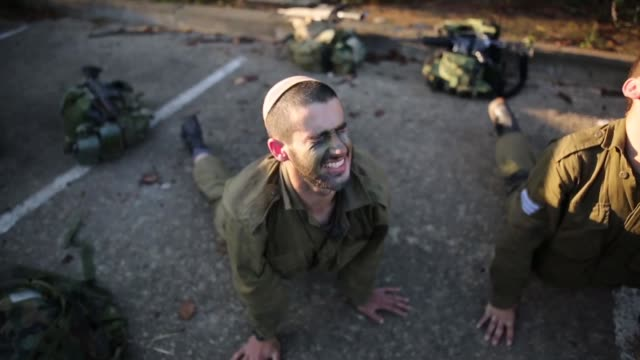 stockvideo's en b-roll-footage met soldiers from the artillery corps carry their comrade on a stretcher while taking part in a baret march at the end of their basic army training on... - israëlisch leger