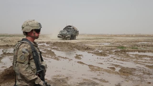 vídeos de stock e filmes b-roll de soldiers from the us army's 4th squadron 2d cavalry regiment move through a muddy field with a stryker vehicle while on patrol with soldiers from the... - kandahar