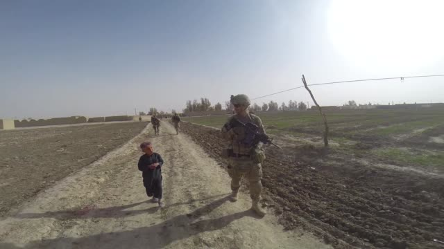 stockvideo's en b-roll-footage met soldiers from the us army's 4th squadron 2d cavalry regiment patrol through a village on march 3 2014 near kandahar afghanistan - kandahar afghanistan