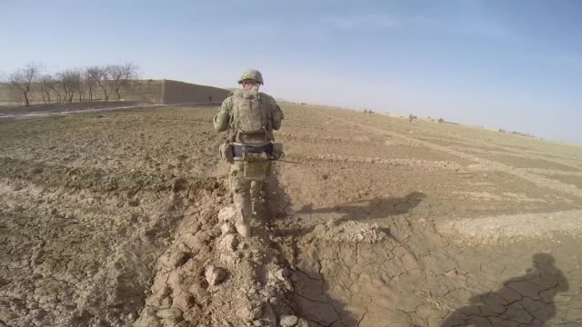 soldiers from the us army's 4th squadron 2d cavalry regiment patrol through a village on march 3 2014 near kandahar afghanistan - afghanistan video stock e b–roll