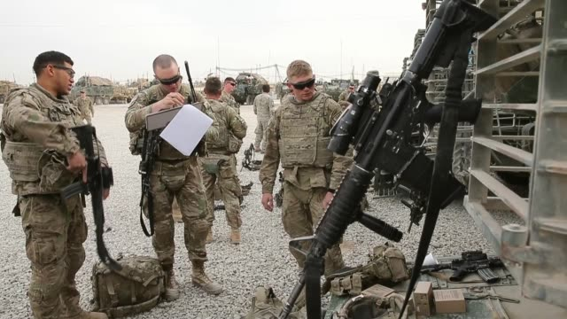 ls soldiers from the us army's 4th squadron 2d cavalry regiment prepare to go out on patrol on march 4 2014 near kandahar afghanistan - 2001年~ アフガニスタン紛争点の映像素材/bロール
