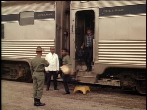 1967 montage soldiers getting off train for boot camp, one having his head shaved, soldiers in line receiving supplies / fort campbell, kentucky, united states - fort campbell video stock e b–roll