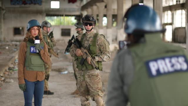 vídeos y material grabado en eventos de stock de soldados dando entrevista a la prensa en la zona de guerra - war