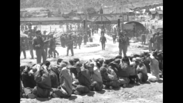 Soldiers guarding North Korean Communist prisoners sitting on ground with hands on heads tank halftrack and prison compound in background / tank...