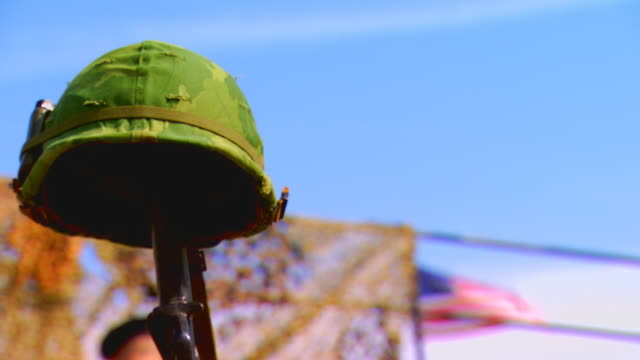 soldier's gun holding up helmet, low angle close up - army helmet stock videos & royalty-free footage