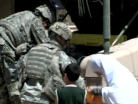 soldiers hand out bags of food and aid supplies to iraqi women and children - iraq stock videos & royalty-free footage