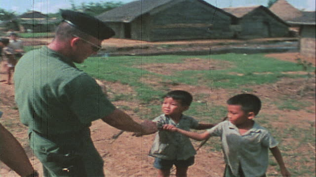soldiers handing out supplies to villagers and a swarming horde of kids / vietnam - south vietnam stock videos & royalty-free footage