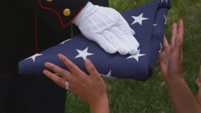 sm cu soldier's hands giving woman folded up us flag/ woman holding flag on her knee/ chicago, il - folded stock videos & royalty-free footage