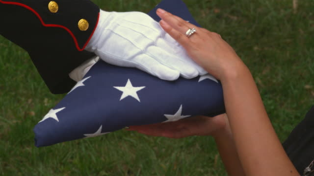 stockvideo's en b-roll-footage met sm cu soldier's hands giving woman folded up us flag/ woman holding flag on her knee/ chicago, il - leger soldaat