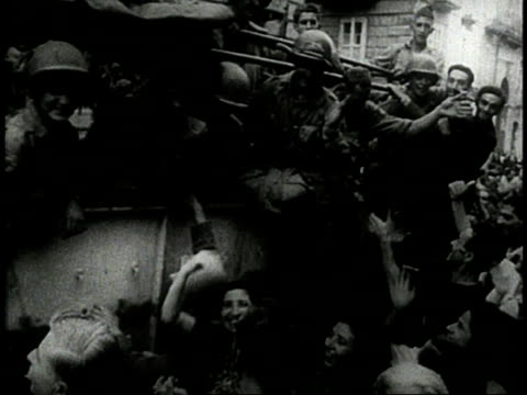 soldiers hang out of trucks as crowd reaches out to them / crowd cheering and waving / europe - 1944 stock videos and b-roll footage