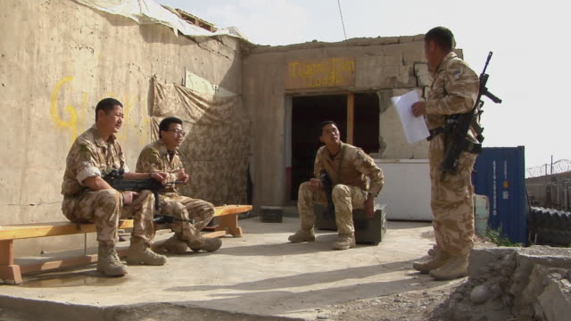 ws soldiers having discussion / musa qala helmand province afghanistan - legs crossed at ankle stock videos and b-roll footage