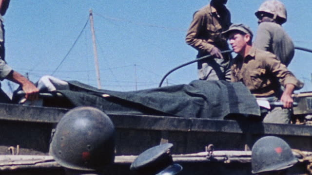 soldiers helping wounded soldiers board dukw on the beach and lifting them aboard on stretchers / iwo jima japan - battle of iwo jima stock videos and b-roll footage