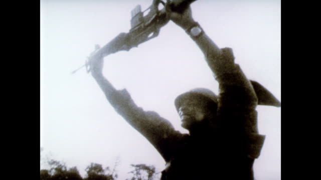 vídeos de stock e filmes b-roll de / soldiers holding rifle above his head / helicopters landing / vietnamese refugees. vietnam war scenes on january 01, 1969 in vietnam - 1969